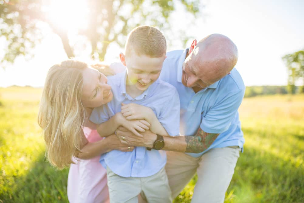 family of 3 photo session at manassas battlefield in a grassy field by alisonbell photographer